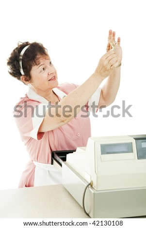 Cashier in a restaurant checks a bill to see if it is counterfeit.  Isolated on white. - stock photo
