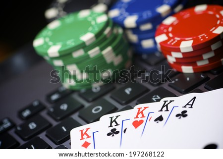 Casino chips and cards stacking on a laptop - stock photo
