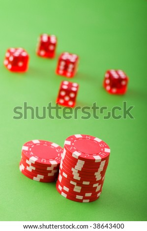 Casino chips and dice against green background - stock photo