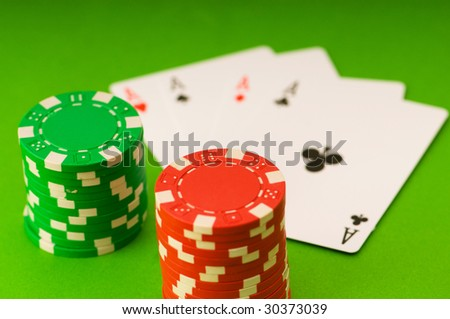 Casino chips and four aces against green background - stock photo