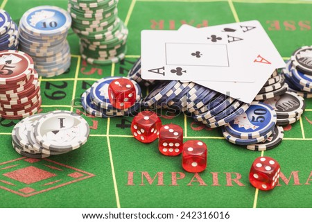 Casino chips, cards and dices on green felt game table - stock photo