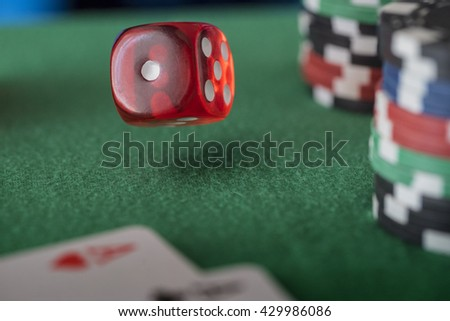 Casino chips, cards and red dices on green felt game table - stock photo