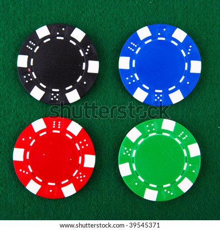 Casino chips each different color on green felt - stock photo