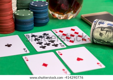 casino chips for gambling, cognac and playing cards, money and phone  on green