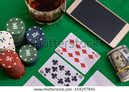 casino chips for gambling, cognac and playing cards, money and phone  on green - stock photo