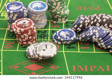 casino chips on green felt game table in a casino  - stock photo
