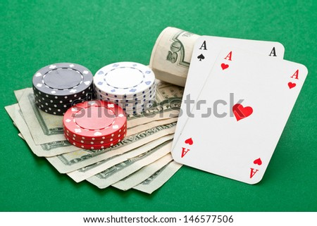 Casino chips with pocket aces on dollar bills on poker table - stock photo