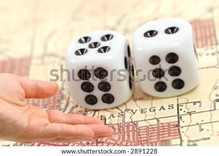 casino concept with hand and dices on map from Las Vegas - stock photo
