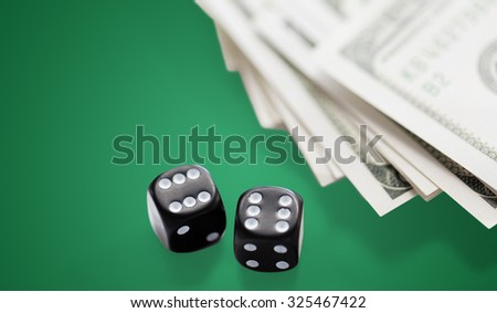 casino, gambling and fortune concept - close up of black dice and dollar cash money on green table background - stock photo