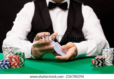 casino, gambling, poker, people and entertainment concept - close up of holdem dealer shuffling playing cards deck and chips on green table - stock photo