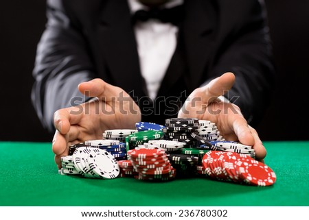 casino, gambling, poker, people and entertainment concept - close up of poker player with chips at green casino table - stock photo