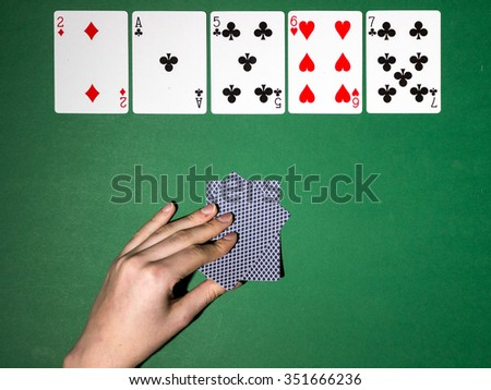 casino, gambling, poker, people and entertainment concept - close up of poker player with playing cards and chips at green casino table over holidays lights background - stock photo