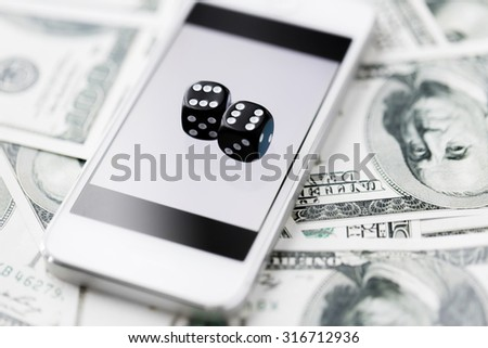 casino, online gambling, technology and fortune concept - close up of black dice, smart phone and dollar cash money - stock photo