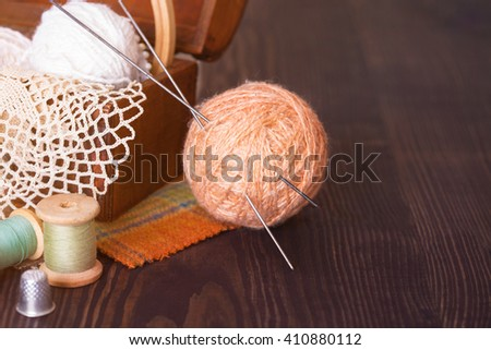 Casket with needlework and beige skein of thread with spokes for knitting on a wooden table - stock photo