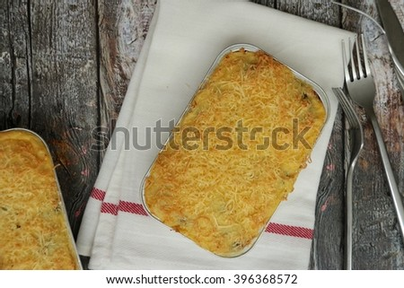 Casserole of potato, broccoli and cheese in disposable aluminium container. Placed on folded white tea towel with red stripe. Few forks are casually left closeby. - stock photo
