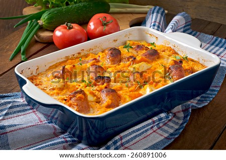 Casserole with sausage, bacon and apples in a pumpkin-cheese sauce - stock photo