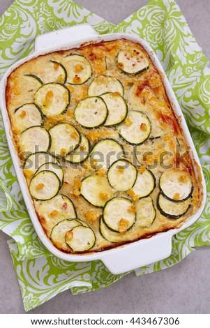 casserole with zucchini, corn, potato and cream in baking dish - stock photo