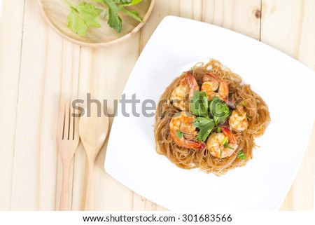 Casseroled prawns/shrimps with glass noodles on wooden background. - stock photo