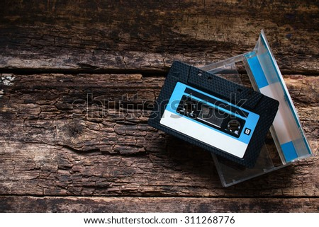 Cassette in an open box on a wooden table - stock photo