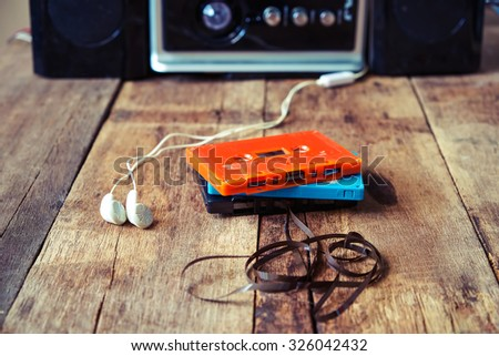 Cassette tape over and Earphone on wooden table vintage effect - stock photo