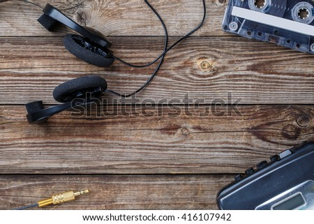 Cassette tapes, cassette player and headphones over wooden table. top view. - stock photo