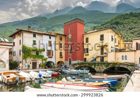 CASSONE, ITALY - JUNE 1: Marina in Lake Garda at Cassone, Italy on June 1, 2015. Lake Garda is one of the most frequented tourist regions of Italy. Foto taken from the port with view to the village. - stock photo