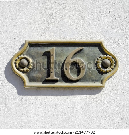 cast bronze house number sixteen on a white stucco wall - stock photo
