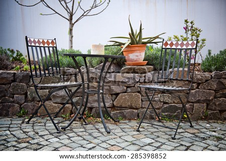 Cast iron garden furniture on a patio with a small table and two chairs standing in the sunshine alongside a walled rock garden with a potted cactus on top of the wall - stock photo