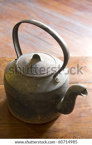 Cast iron kettle over wooden table - stock photo