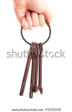 Cast iron keys on a ring, held in a hand. - stock photo