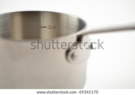 Cast iron measuring cup on a white background - stock photo