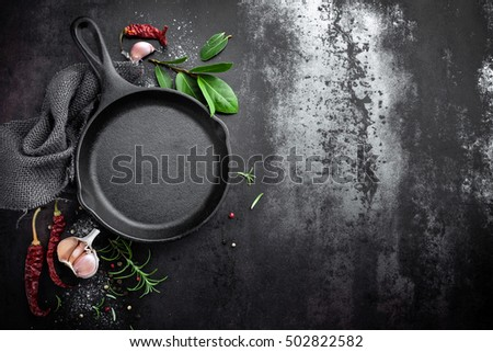 cast iron pan and spices on black metal culinary background, view from above