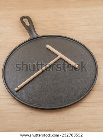 Cast iron pan for baking pancakes and wooden spatula to create pancakes. - stock photo
