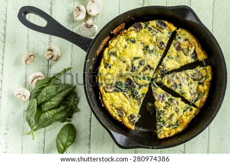 Cast iron skillet filled with a spinach mushroom and onion frittata with raw ingredients - stock photo