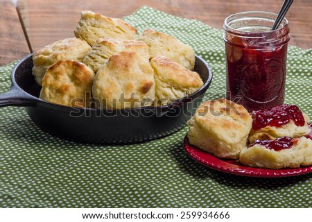 Cast iron skillet of fresh biscuits or scones with jam or jelly - stock photo