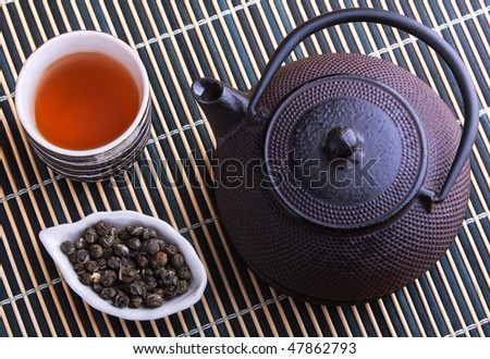 Cast iron TeaPot with teacup and tea leaves on a bamboo mat - stock photo