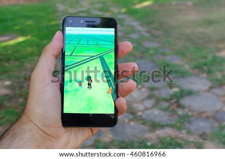 CASTELLON, JULY 2016 - A hand's man plays Pokemon Go with a smartphone in the park.