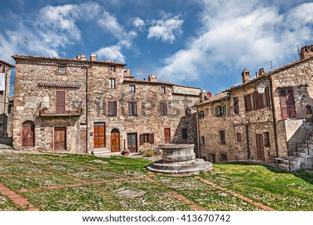Castiglione d'Orcia, Siena, Tuscany, Italy: picturesque square with an ancient water well and cobblestone pavement in the italian old town   - stock photo