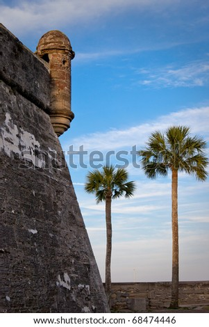 Castillo de San Marcos outer wall with two palm trees. - stock photo