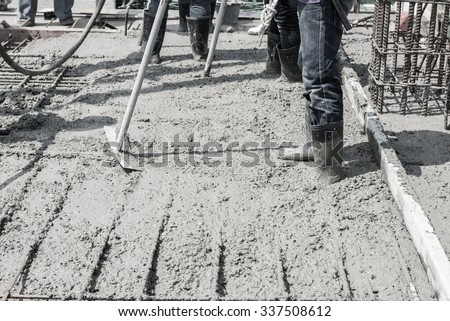 casting concrete cement work. leveling concrete slab floor work step of the building construction by worker.sepia color tone for old feel - stock photo
