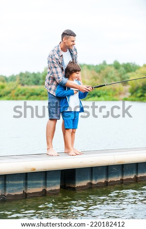 Casting off together. Father and son fishing together while standing on quayside together - stock photo