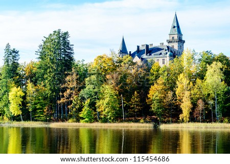 Castle in scenic view surrounded by forest in autumn. Lake in foreground. Castle was built and given as wedding gift.