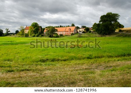 Castle of in Denmark, Scandinavia with its green and lush fields in the foreground.
