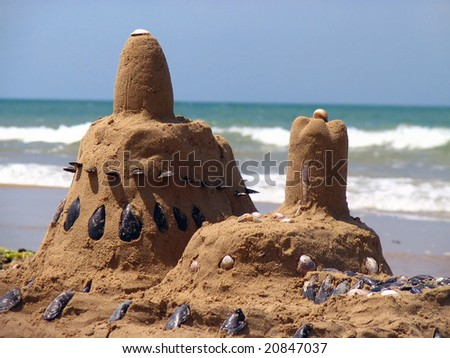 Castle on the beach made from sand and shells - stock photo