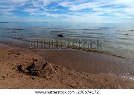 Castle on the sand broken by waves - stock photo