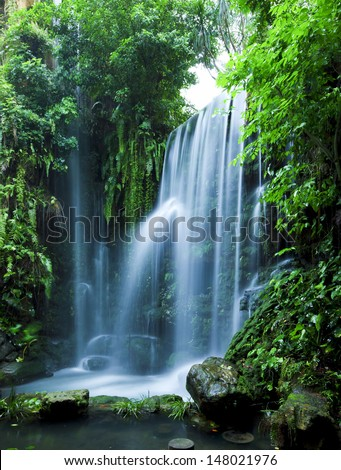 Castle ruins surrounded by rainforest gardens, right beside a stunning waterfall. - stock photo