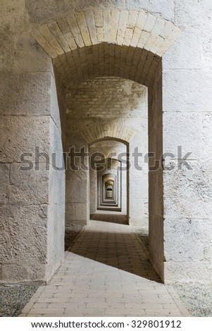 Castle tunnel interior with a series of symmetric arches in a bastion fortress. - stock photo