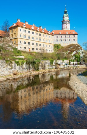 Castle with the famous round tower in Cesky Krumlov, Czech Republic is reflecting in the river Vltava  - stock photo