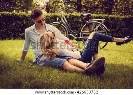 Casual adult couple dressed casual lying on the lown in summer park.
