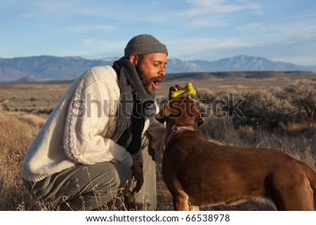 Casual African American man playing with and talking to his dog - stock photo
